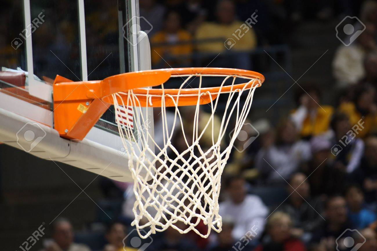basketball rim in focus with a glass backboard stock photo