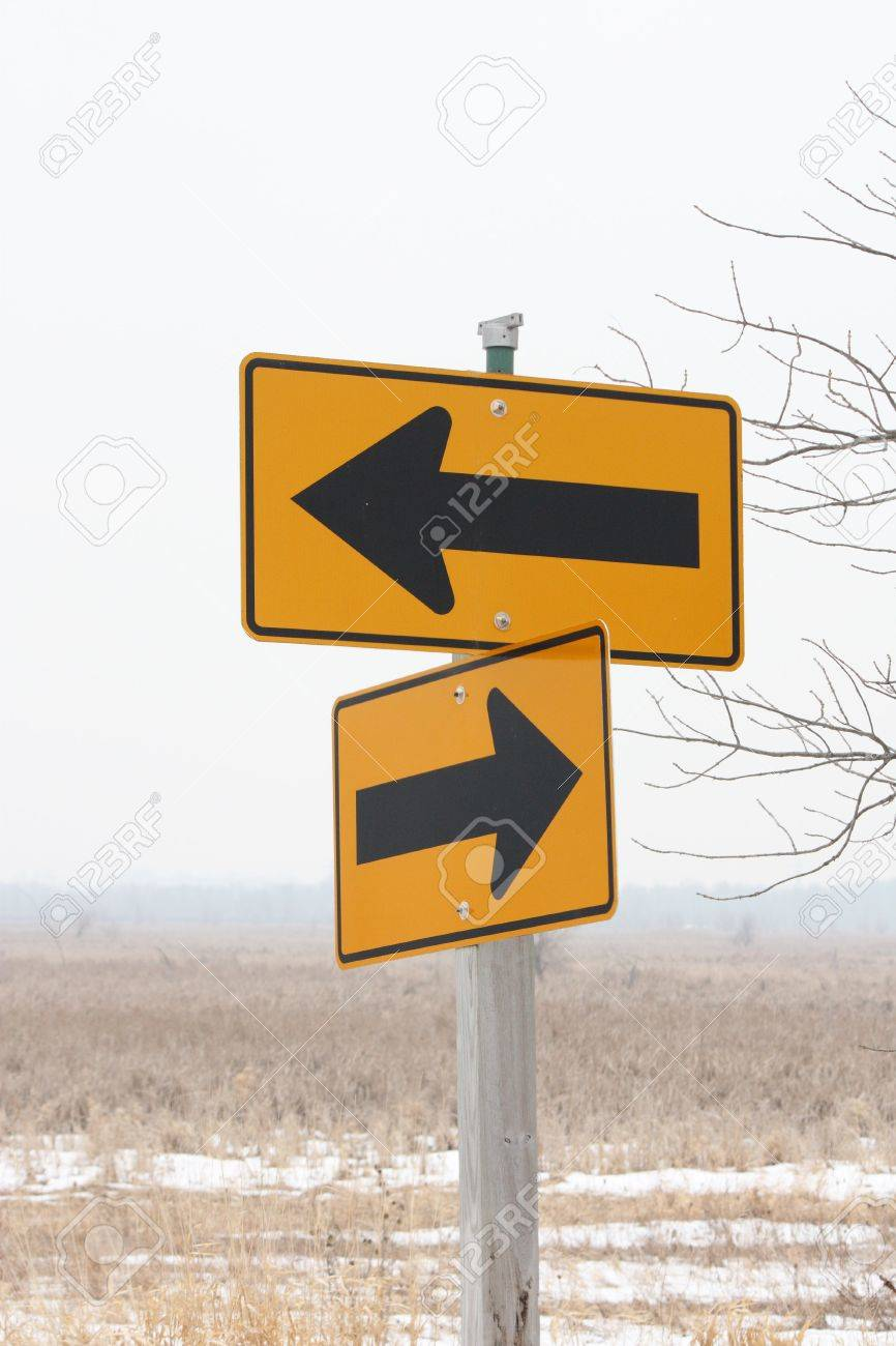 Two arrow signs pointing in contrasting directions.  Which way to go. Stock Photo - 4342689