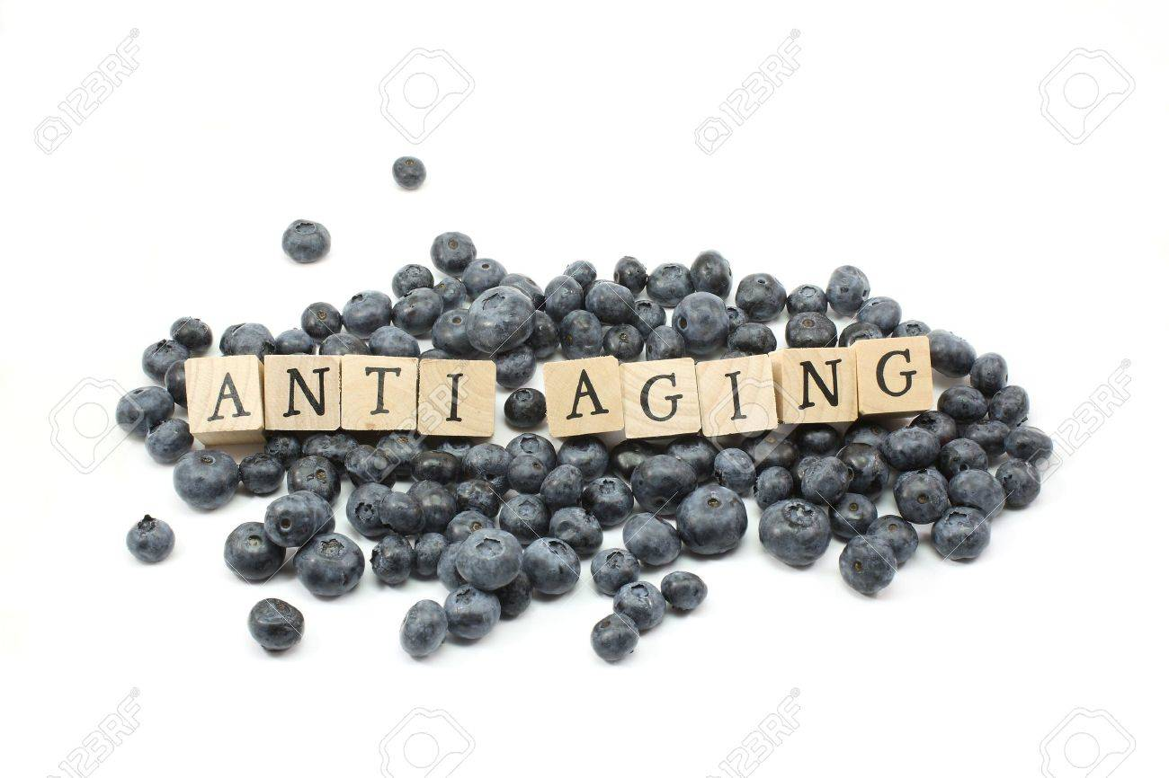 Anti Aging wooden blocks on blue berries. Stock Photo - 5262725