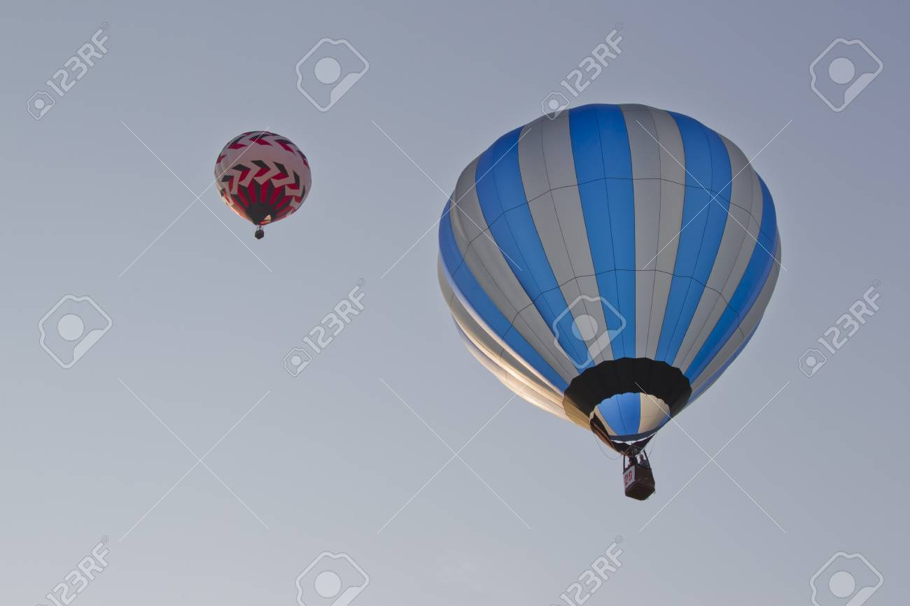 SEYMOUR, WI - AUGUST 3: A red and white balloon and a Silver and blue striped hot air balloon up in the sky at the Balloon Rally at the Annual Hamburger Festival on August 3, 2012 in Seymour, Wisconsin. Stock Photo - 14915024