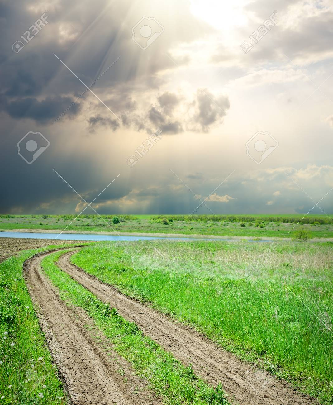 rural road in green grass under dramatic sky Stock Photo - 9623413