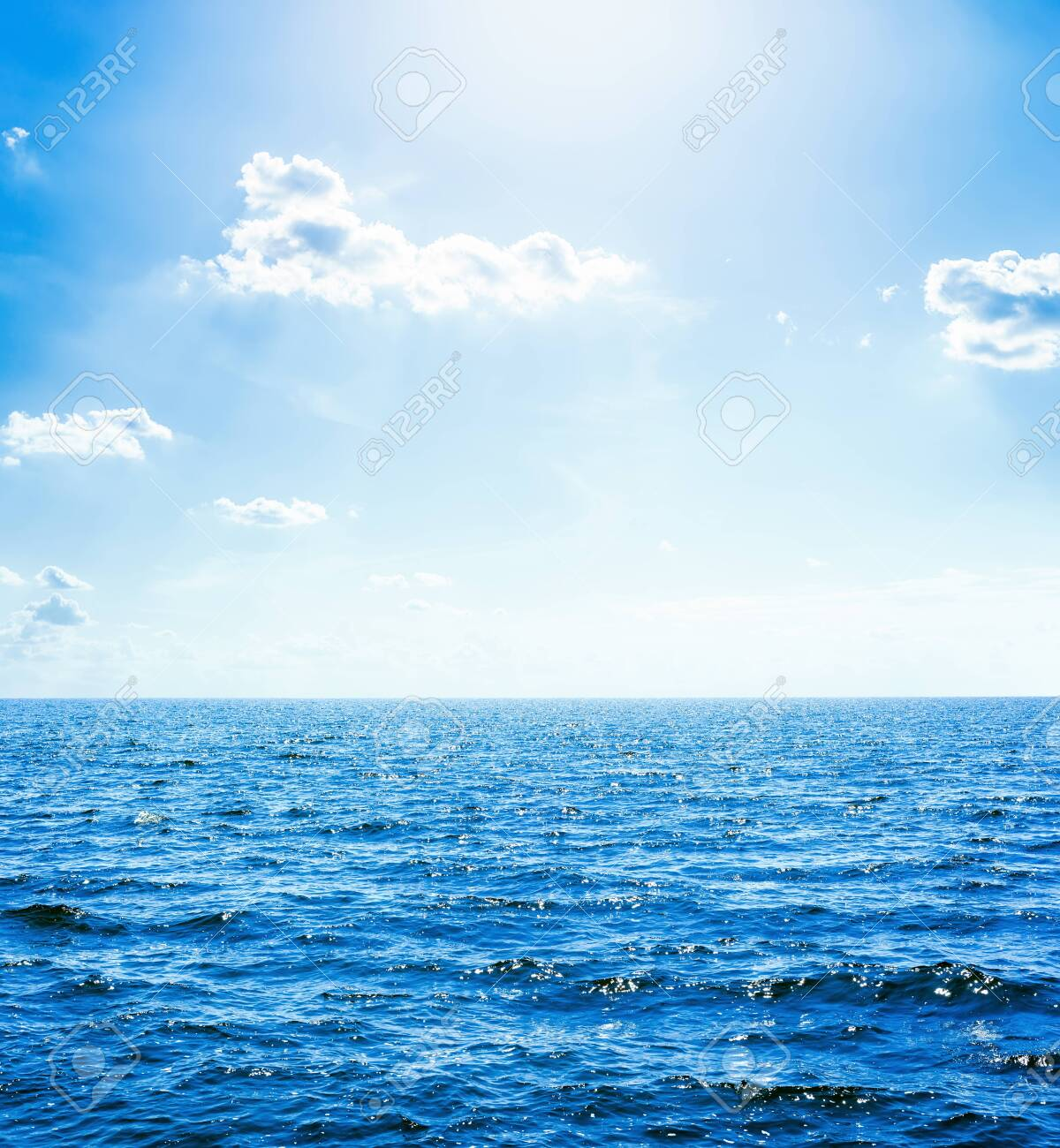 deep blue water in sea and sun with clouds in sky - 129736186