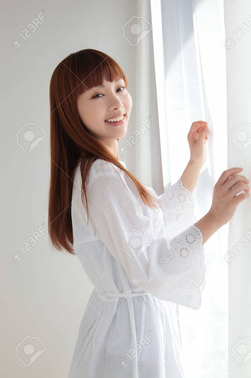 Beautiful young Asian woman by the window Stock Photo - 11322725