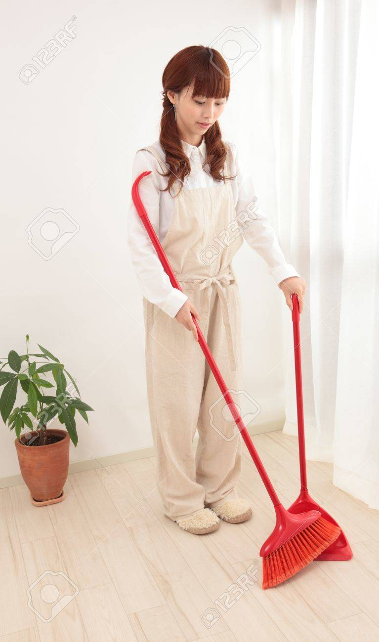 Young Asian woman with a broom to clean up Stock Photo - 11322721