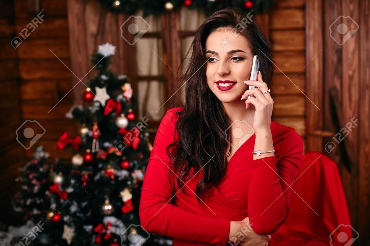Junge Frau Im Roten Kleid Auf Dem Handy Zu Weihnachten Dekoriert ...