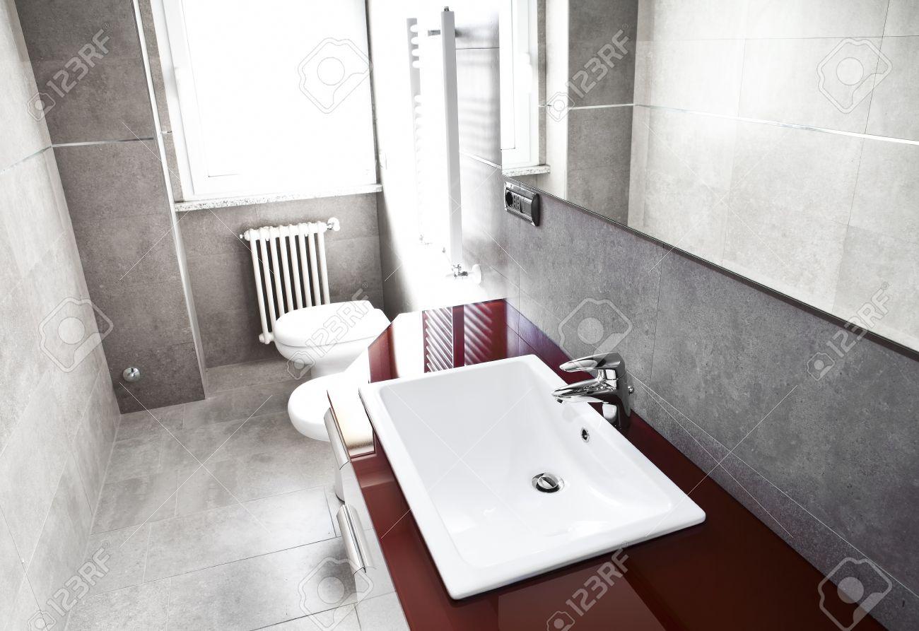 Salle de bain avec toilette rouge, bidet, chauffe-eau, lavabo et miroir sur  un contraste élevé