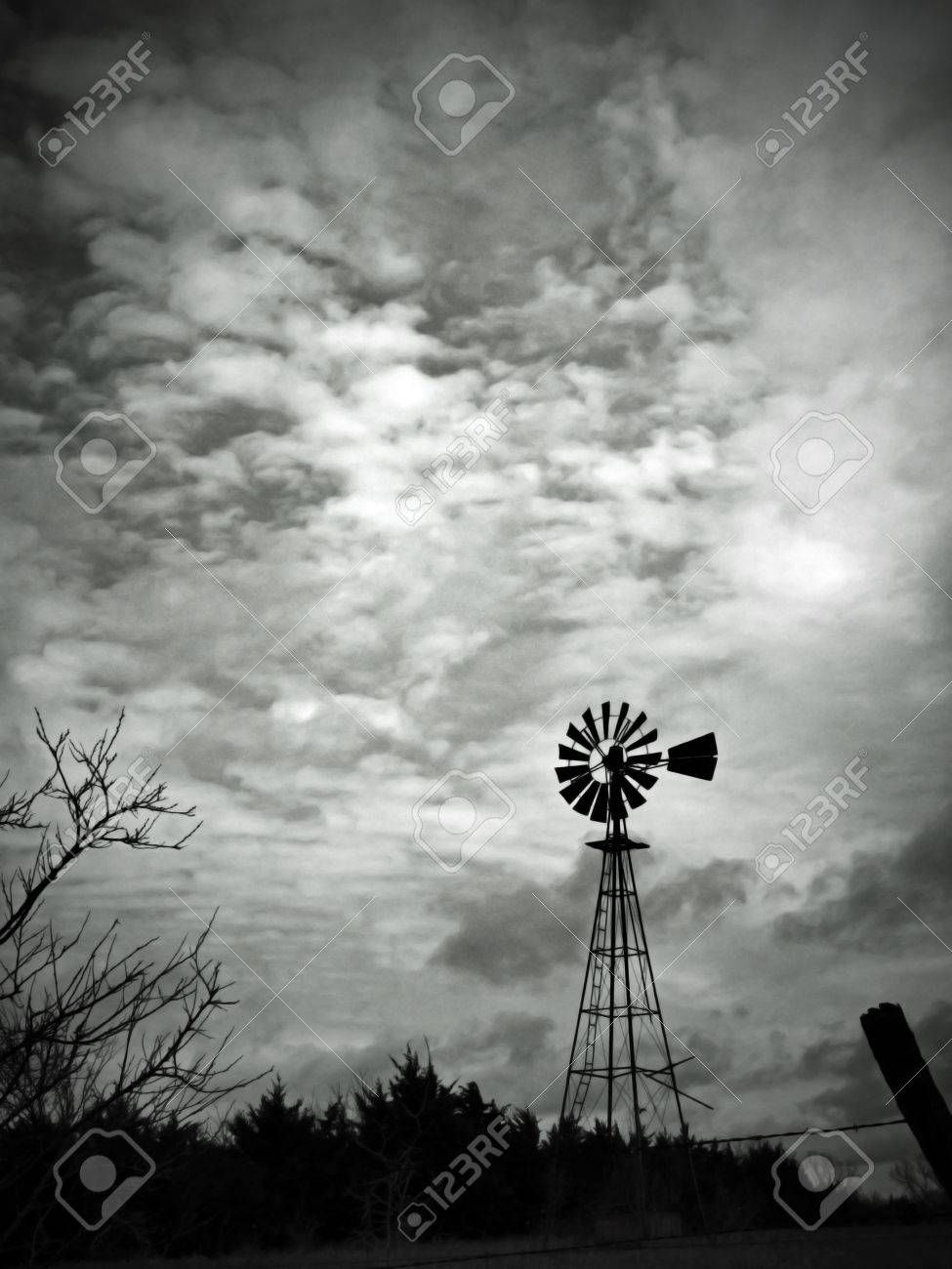 This Black And White Image Features A Lonely Old Fashioned Windmill