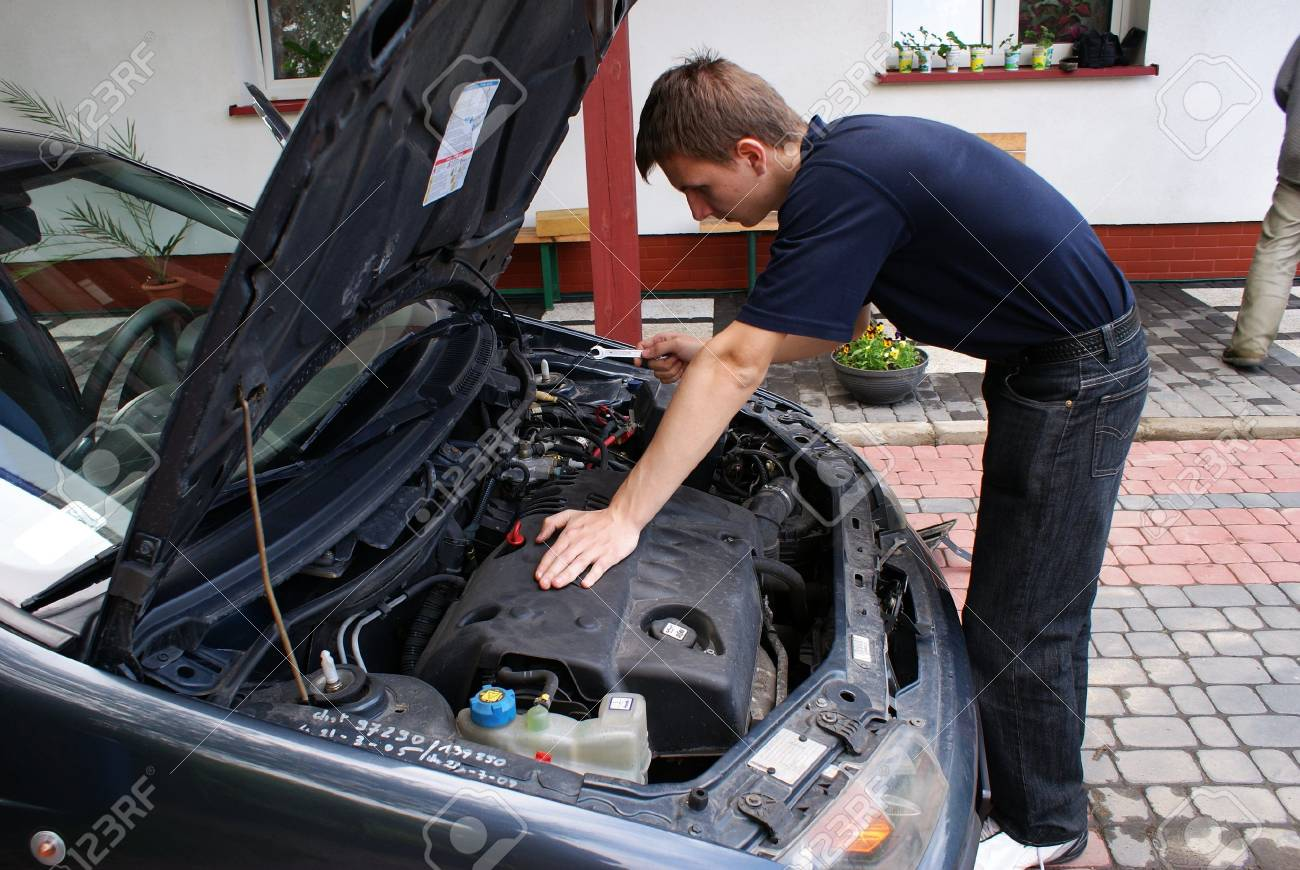 This is a car mechanic next to the engine of small city car