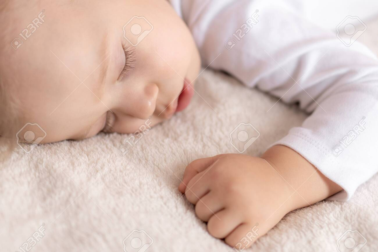 Childhood, sleep, rest, family, lifestyle concept - close-up portrait of a cute little boy of 2 years old in a white body sleeping on a beige bed at noon with mouth open top and side view. - 145842370