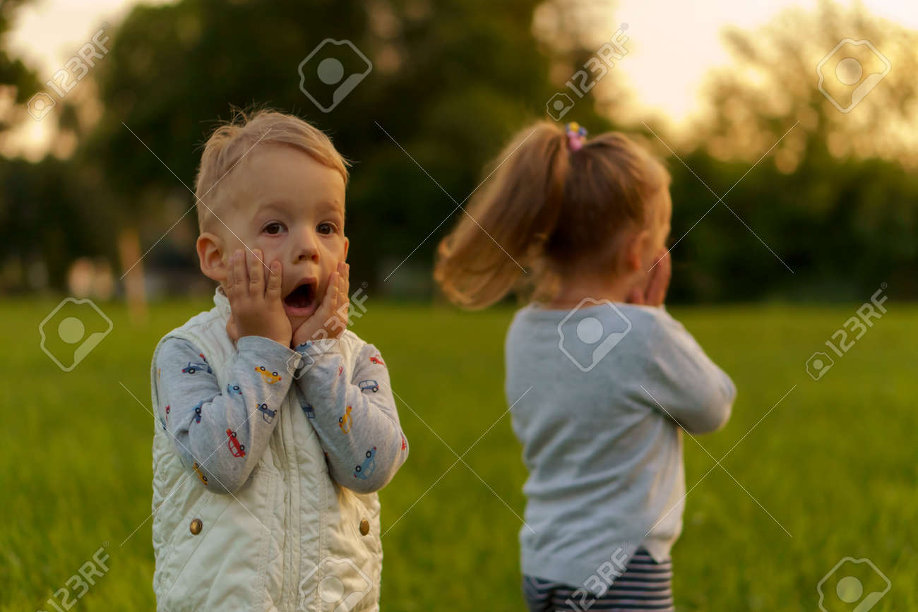 infancy, childhood, development, autumn mood, medicine and health concept - two small children boy and girl of same age, demonstrate emotions of fear and surprise on green meadow in park at sunset. - 154201192
