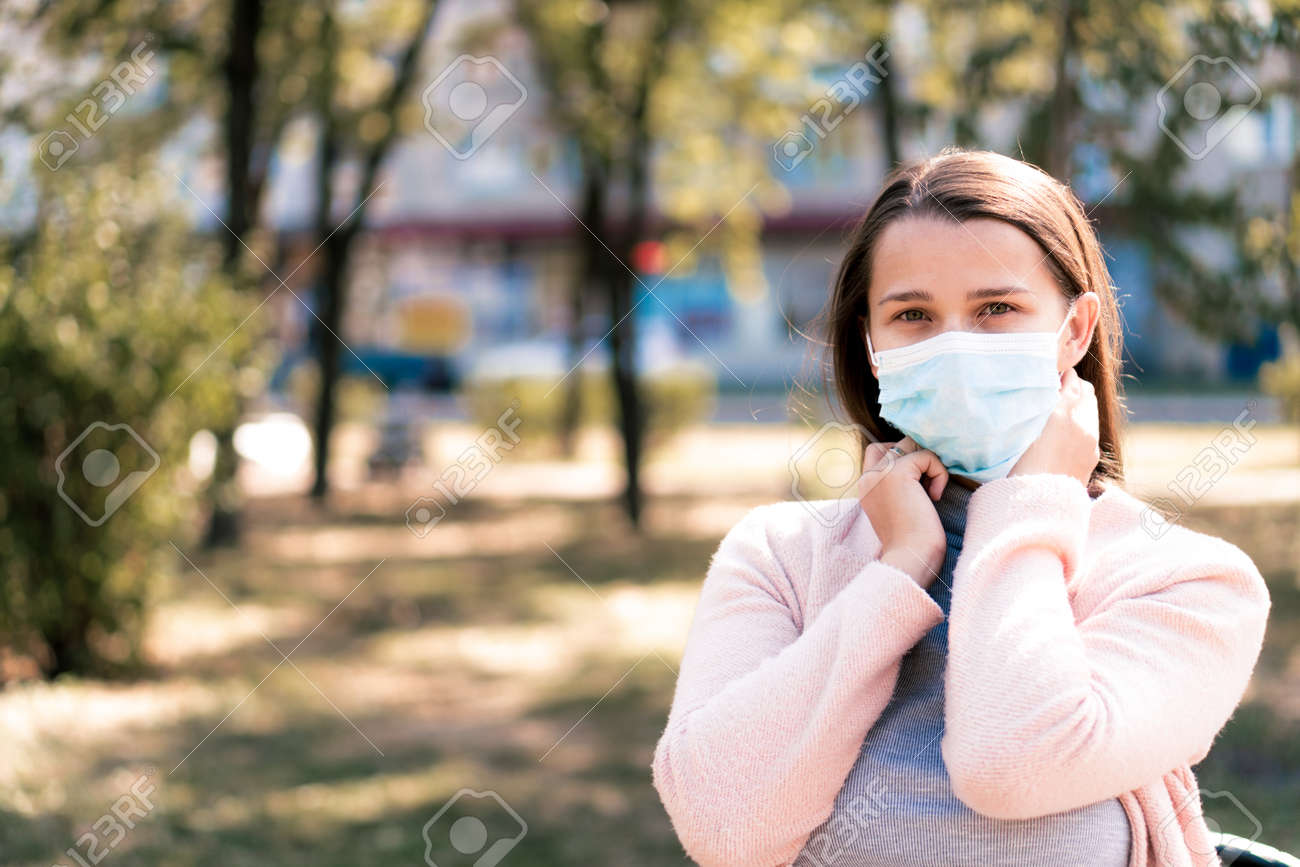 care, infants, spring, quarantine concept - Young cute long haired woman European Caucasian Slavic appearance put on blue medical protective mask in midday sunlight backlight in park. - 164640281