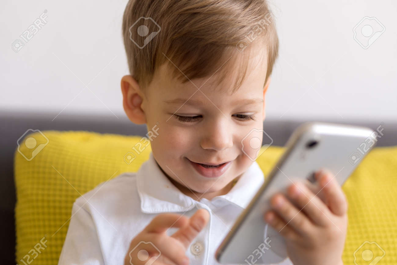 close-up happy little cute preschool baby boy talking video conference by smartphone in living room at home on yellow gray sofa with happiness smile. Childhood, online communication, tehnology concept - 166788937