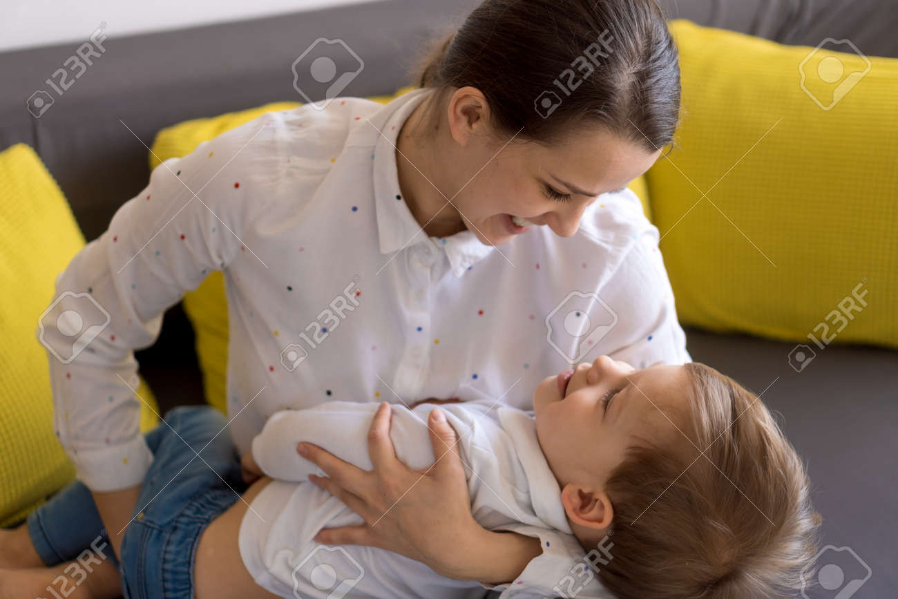 caucasian family little preschool baby boy and mom young woman hug joyfully together in living room at home with happiness smile. Child son congratulates on Mothers Day. Motherhood, childhood concept - 166788939