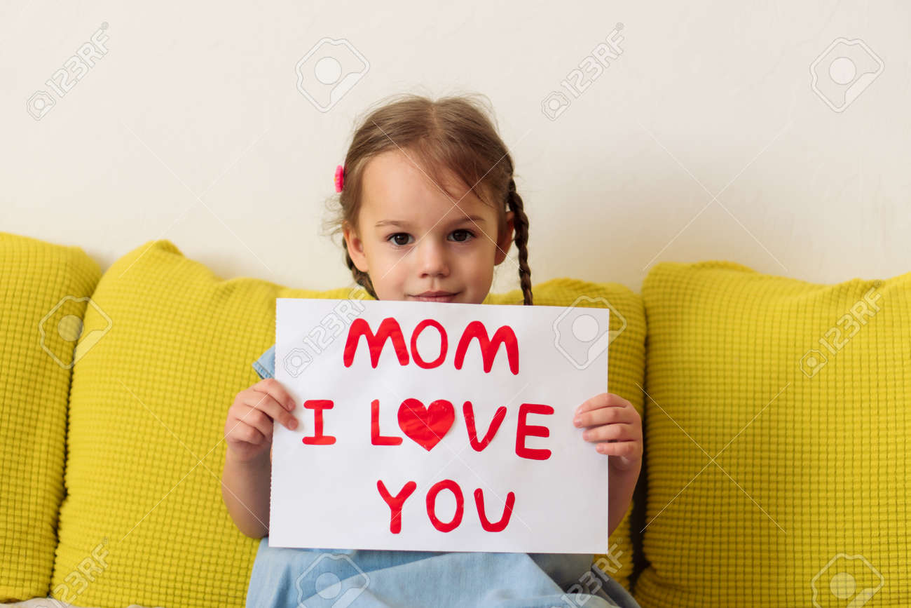 smiling little preschool child girl holding greeting card for Happy Mothers Day with drawn red heart. Loving caucasian baby wishes mom happy birthday confesses his love. Motherhood, childhood concept - 166788940