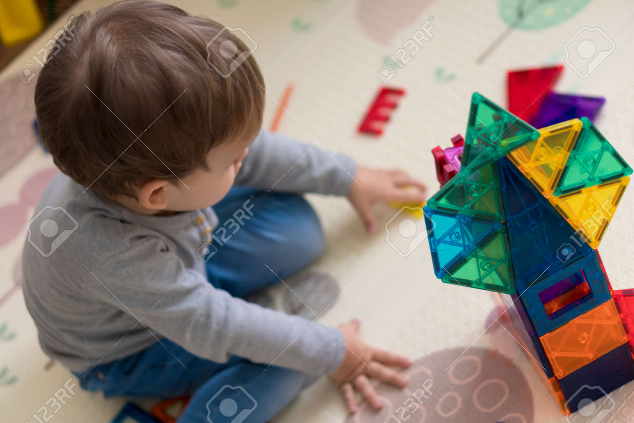 close-up little cute preschool child boy 2-3 years builds building from colored magnetic construction. Baby plays in kids room. child creates tower of geometric shapes. Childhood, tehnology concept - 166788941