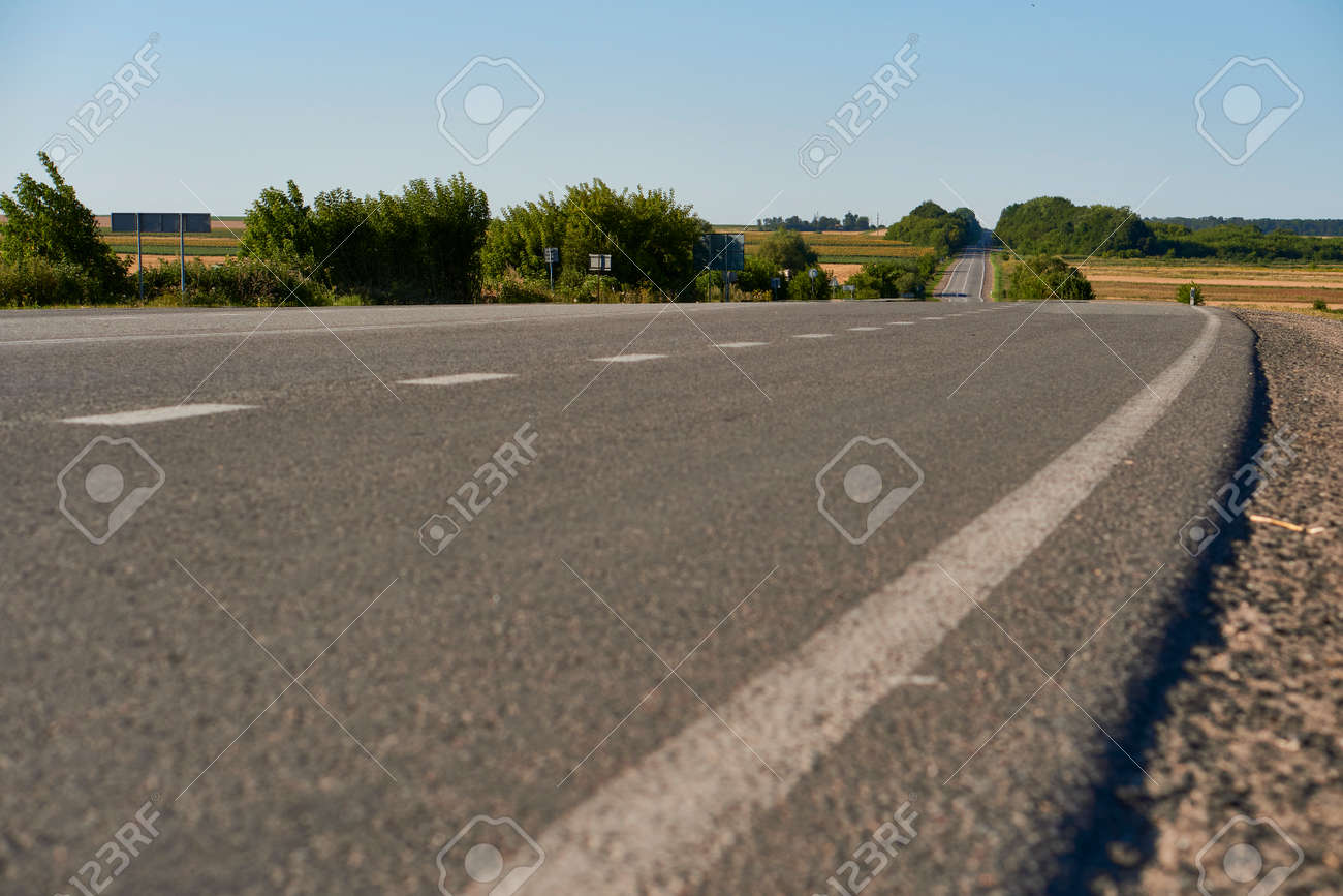 soft focus asphalt road surface with white markings close-up from the low shot. blured country road and field with forest in summer. High quality photo. Travel, tehnology, nature comcept. - 166761871