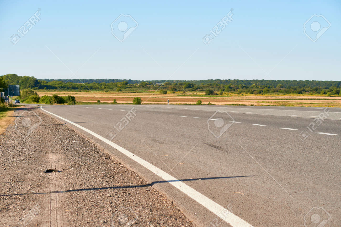 soft focus asphalt road surface with white markings close-up from the low shot. blured country road and field with forest in summer. High quality photo. Travel, tehnology, nature comcept. - 166761905