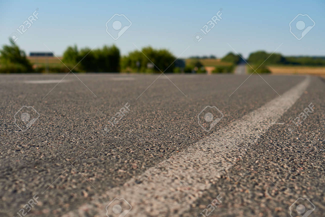 soft focus asphalt road surface with white markings close-up from the low shot. blured country road and field with forest in summer. High quality photo. Travel, tehnology, nature comcept. - 166781830