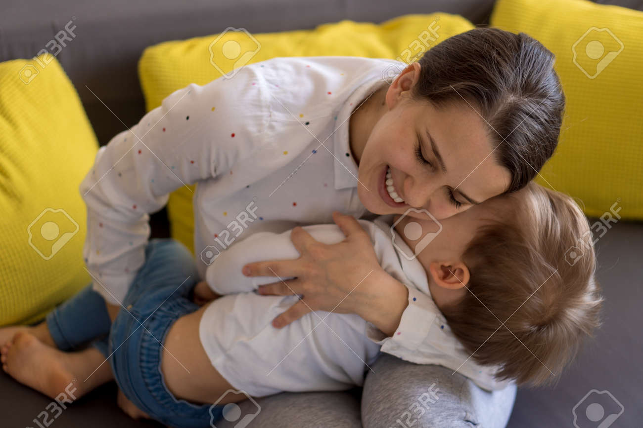 caucasian family little preschool baby boy and mom young woman hug joyfully together in living room at home with happiness smile. Child son congratulates on Mothers Day. Motherhood, childhood concept - 166845706