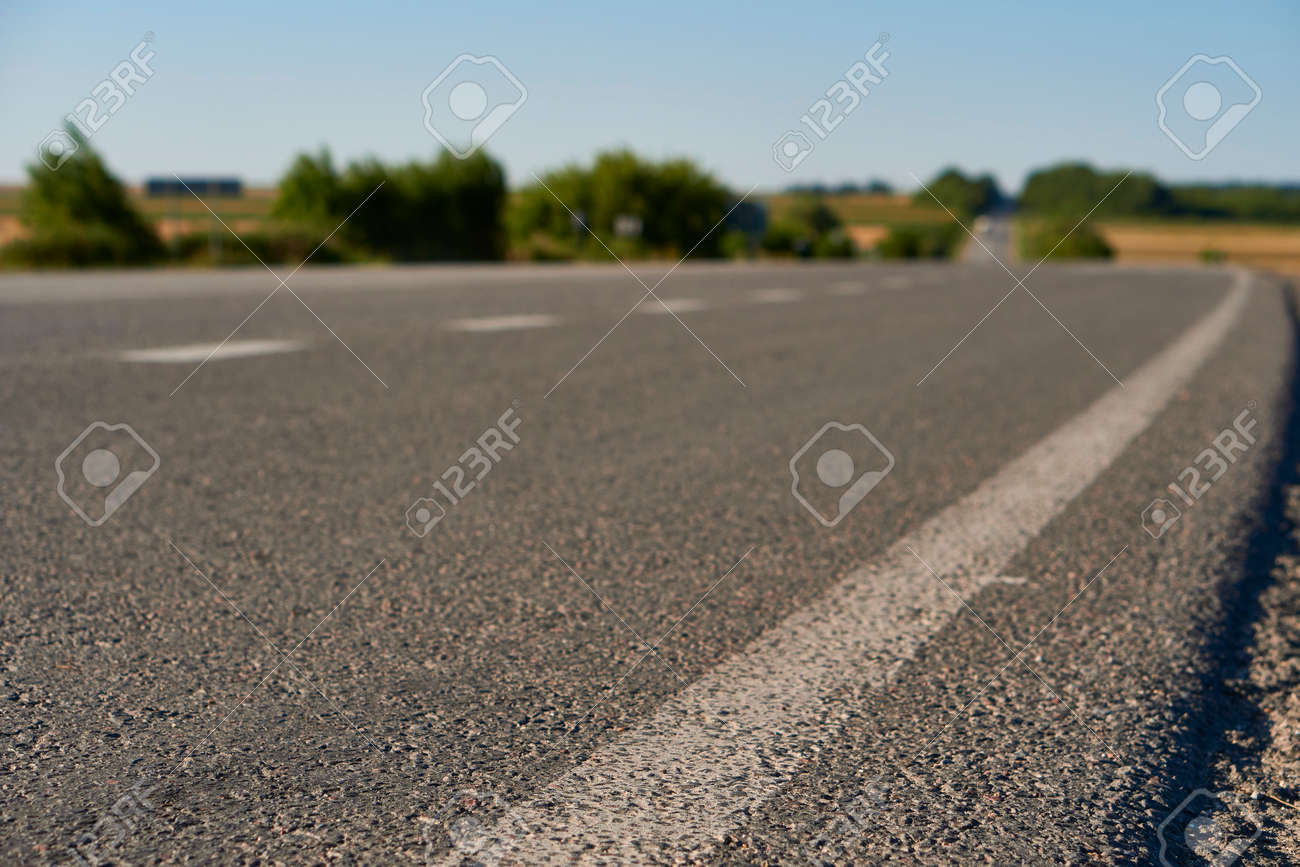 soft focus asphalt road surface with white markings close-up from the low shot. blured country road and field with forest in summer. High quality photo. Travel, tehnology, nature comcept. - 166844998