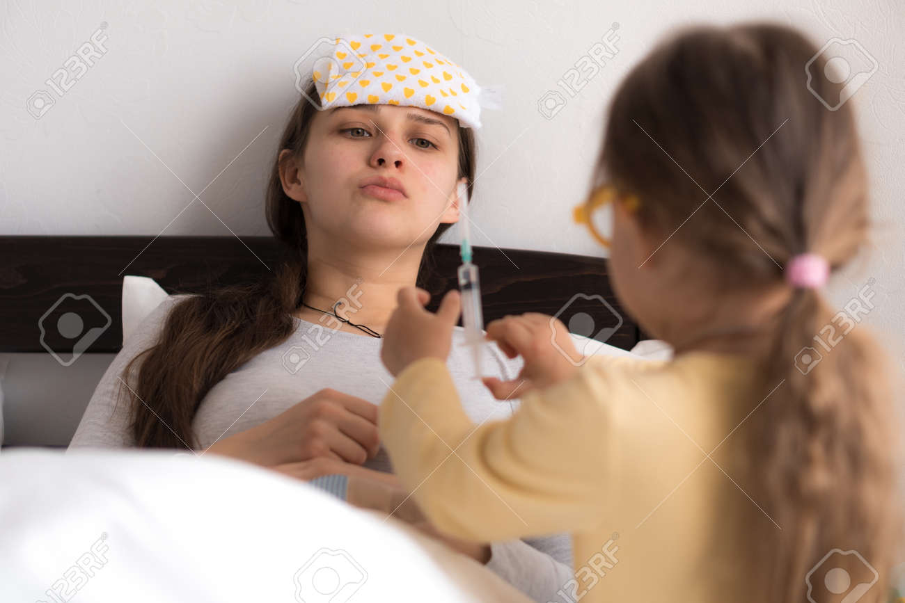 Cute little girl wearing uniform playing doctor or nurse with young mum or nanny in bedroom, makes an injection, measures temperature, family spending leisure time at home together, role play game - 167137544