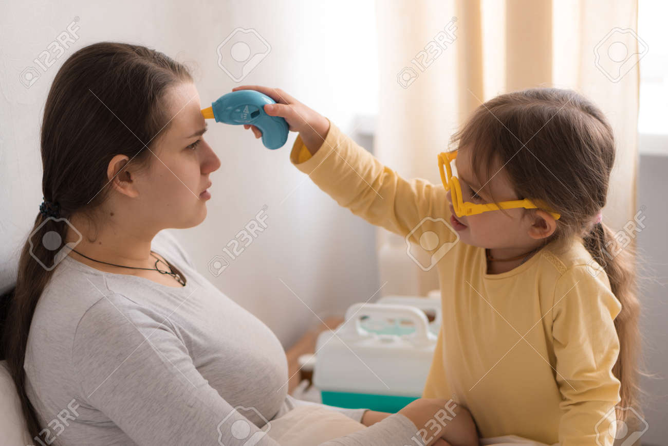 little girl wearing uniform playing doctor, nurse with young mum, nanny in bedroom, checking mother throat, measures temperature, take care, family spend leisure time at home together role play game - 167137546