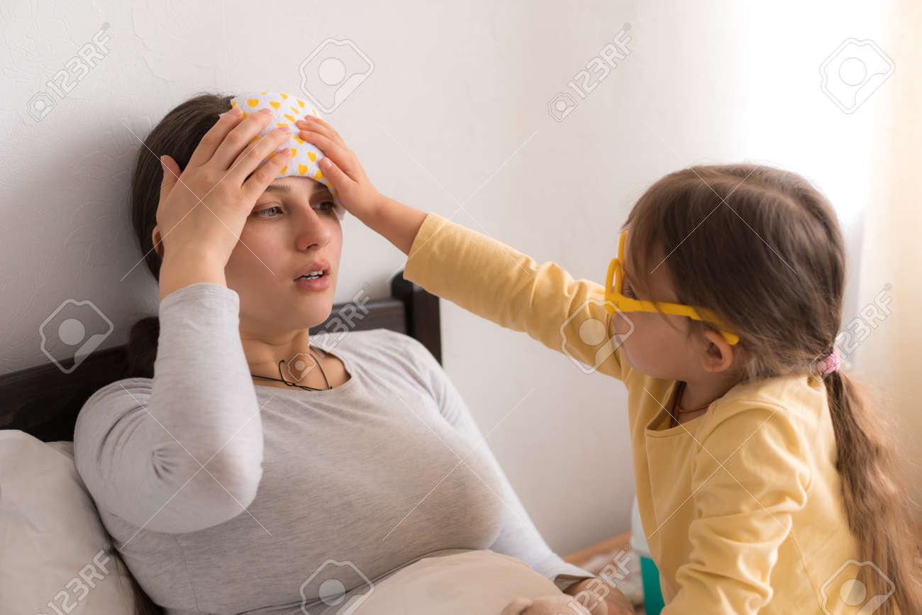 little girl wearing uniform playing doctor, nurse with young mum, nanny in bedroom, checking mother throat, measures temperature, take care, family spend leisure time at home together role play game - 167137583