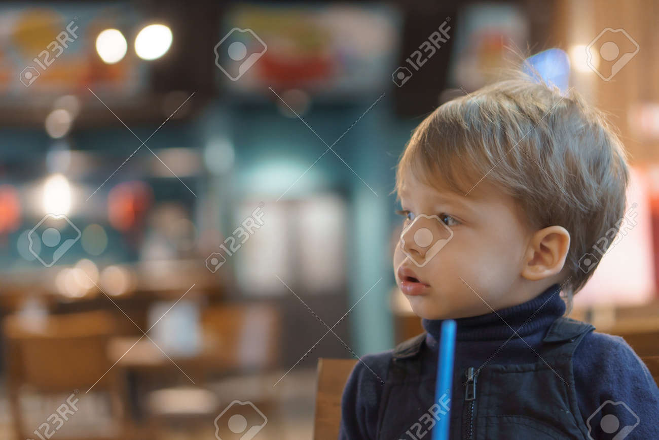 authentic portrait little handsome blond sad boy sitting in cafe in evening alone. Preschool toddler kid child eating and drinking fast food lunch in restaurant. Family, childhood, health, rest - 167093102