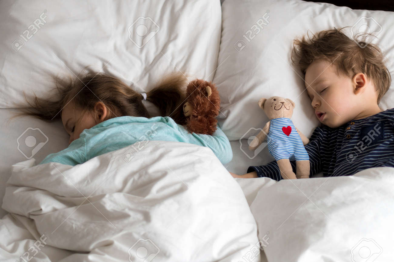 Authentic portrait cute caucasian little preschool siblings baby boy and girl in blue sleep with teddy bear on white bed. child resting at lunchtime. care, medicine and health, Childhood, life concept - 167094233