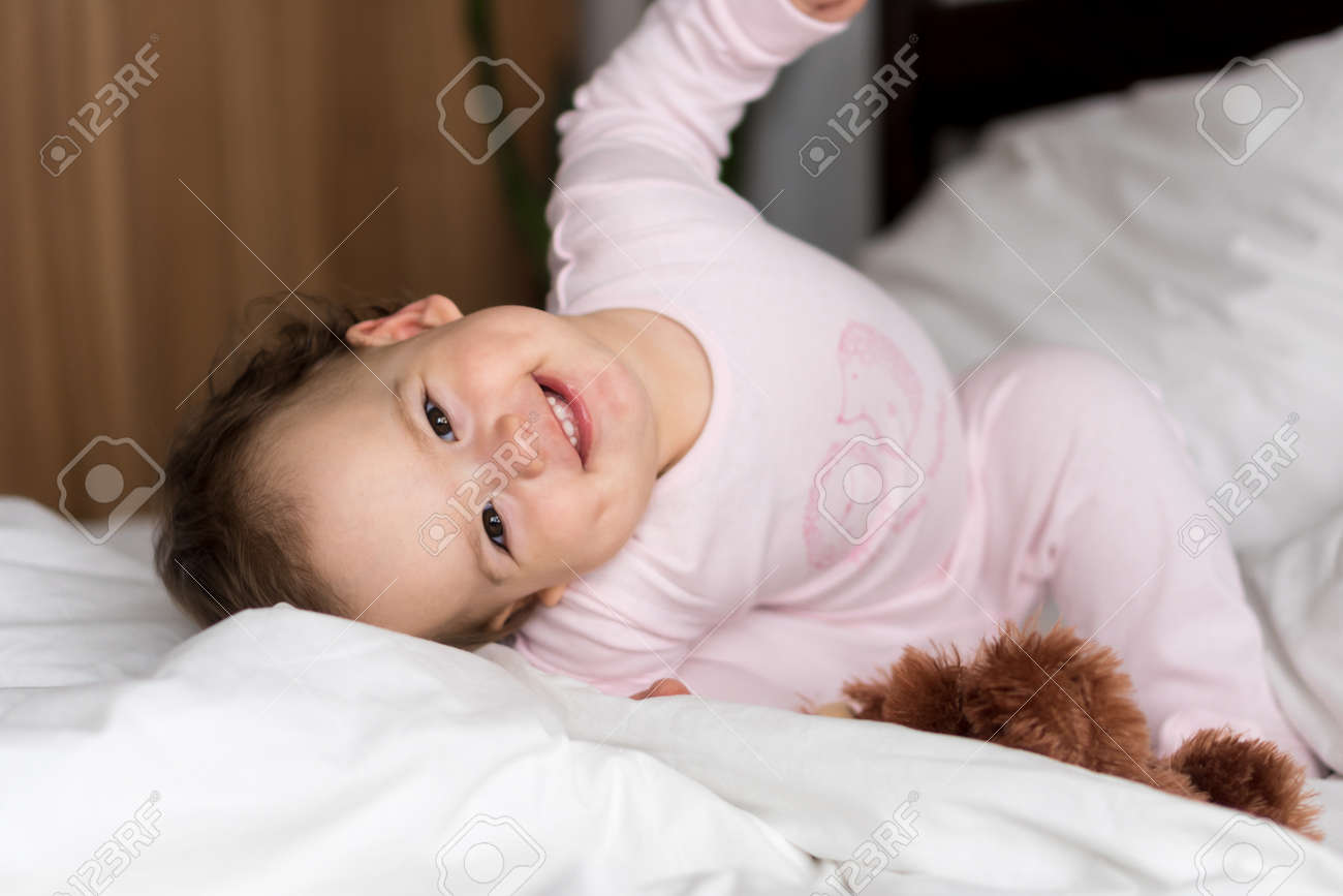 Authentic portrait caucasian little infant chubby baby girl or boy in pink sleepy upon waking looking at camera smiling cute and grimaces in white bed. Child care, Childhood, Parenthood, life concept - 167358744