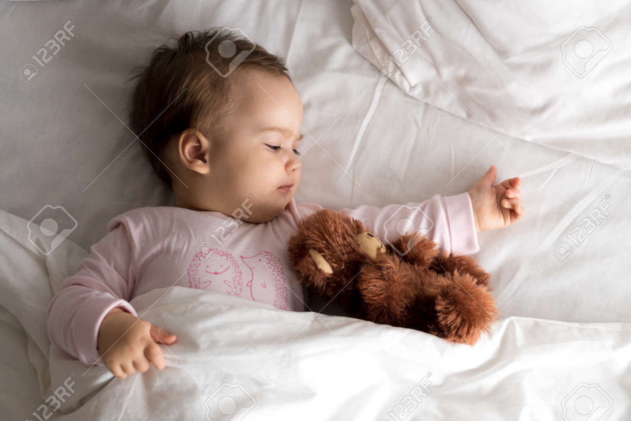 Authentic portrait cute caucasian little infant chubby baby girl or boy in pink sleepy upon waking with teddy bear looking at camera in white bed. Child care, Childhood, Parenthood, lifestyle concept - 167359907