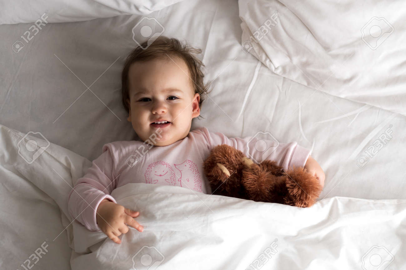 Authentic portrait cute caucasian little infant chubby baby girl or boy in pink sleepy upon waking with teddy bear looking at camera in white bed. Child care, Childhood, Parenthood, lifestyle concept - 167423843