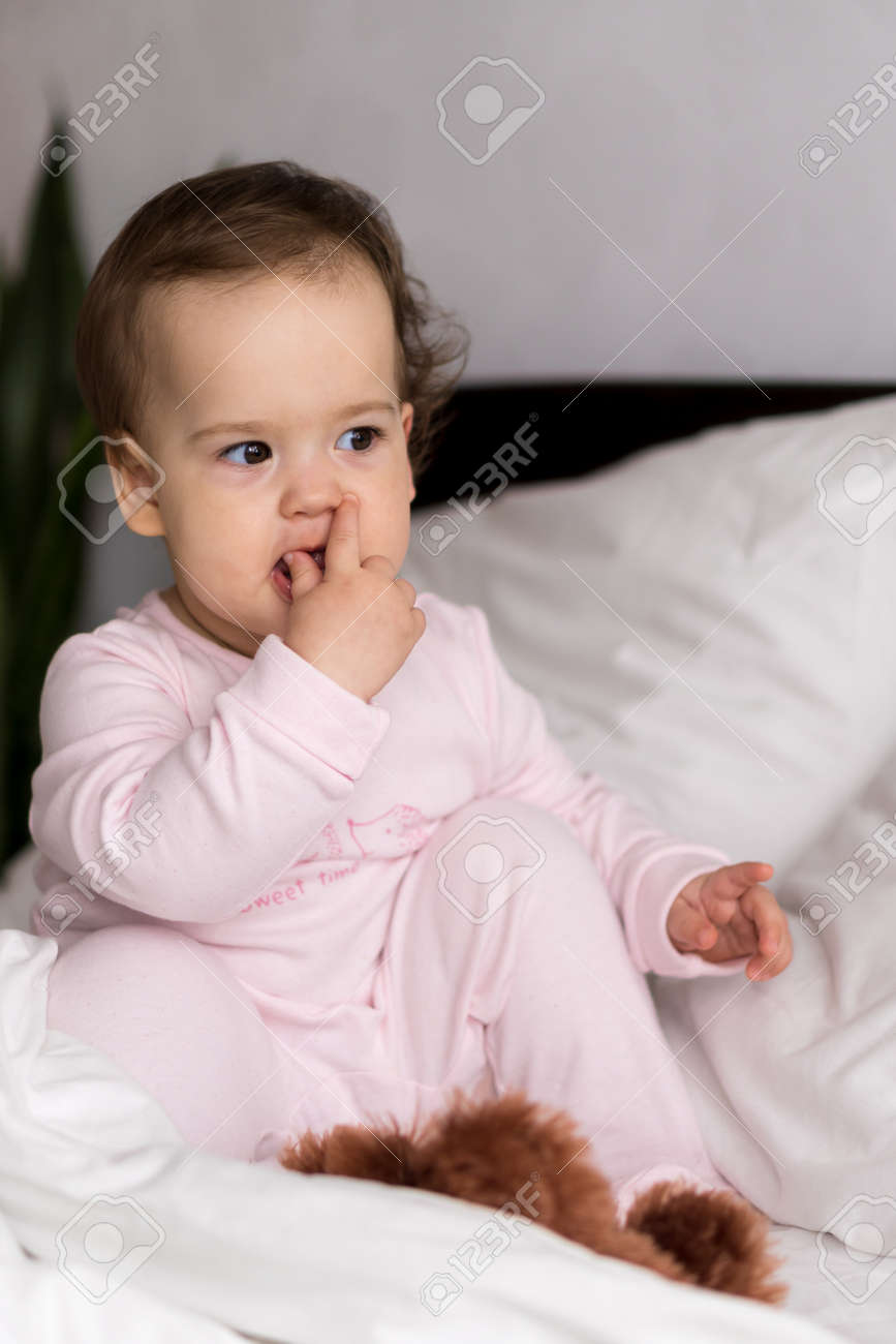 Authentic portrait cute caucasian little infant chubby baby girl or boy in pink sleepy upon waking looking at camera in white bed. Child care, Childhood, Parenthood, lifestyle concept - 167493819