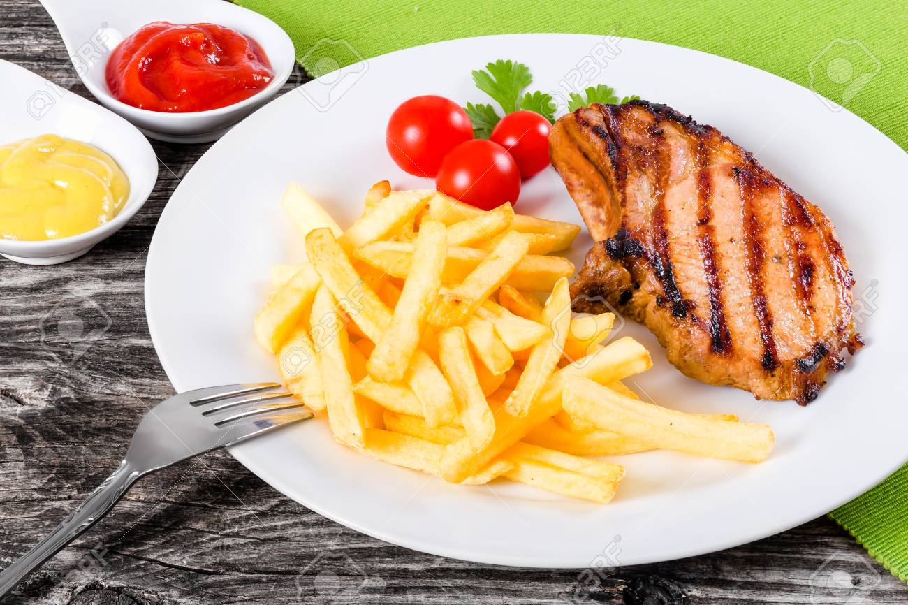 Grilled Pork Chops On A White Dish With French Fries, Cherry.. Stock ...