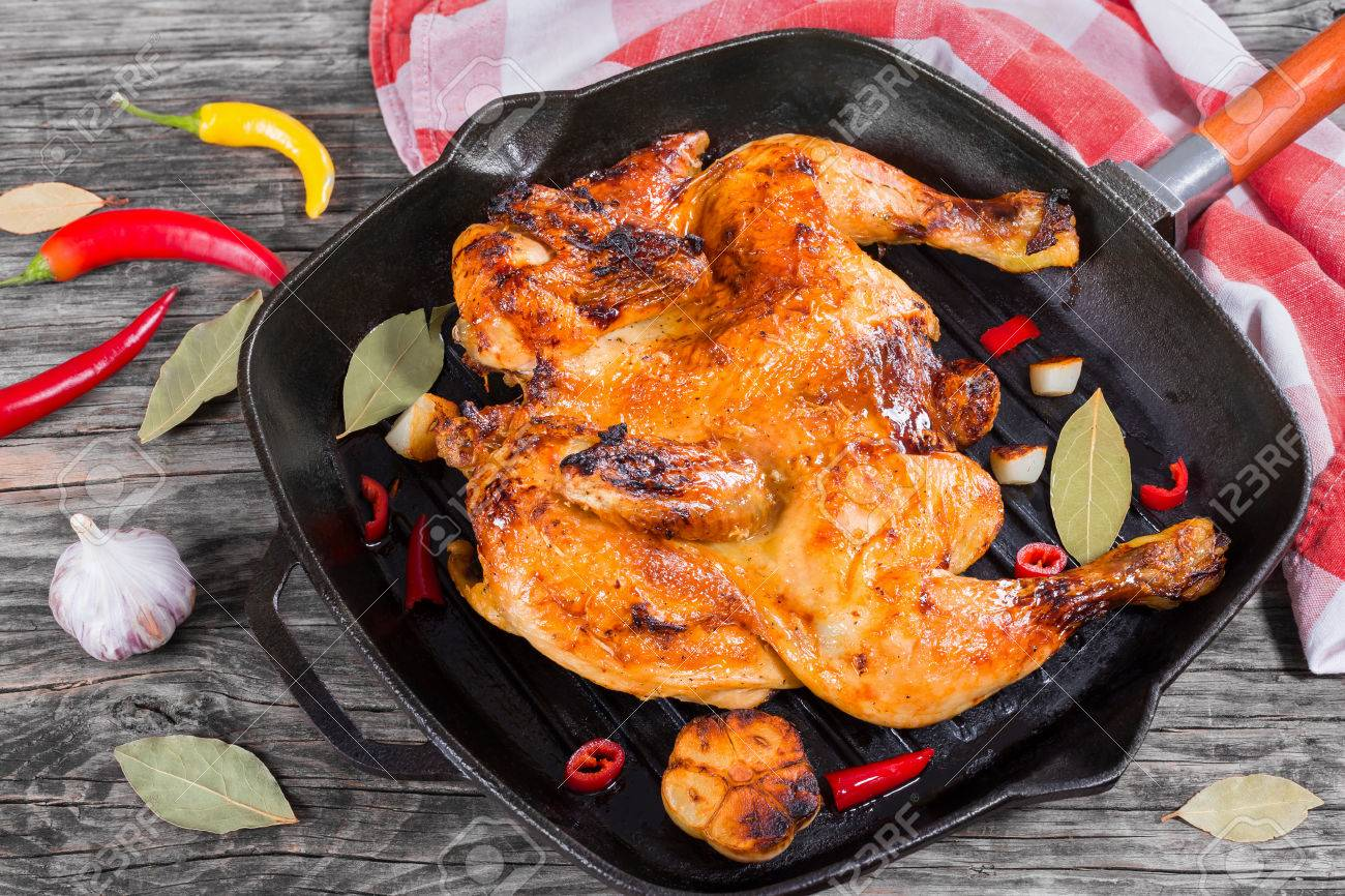 Grilled whole chicken marinated in honey and soy sauce in grill pan with garlic, bay leaves and pieces of chili on rustic table and kitchen towel, view from above - 60856280