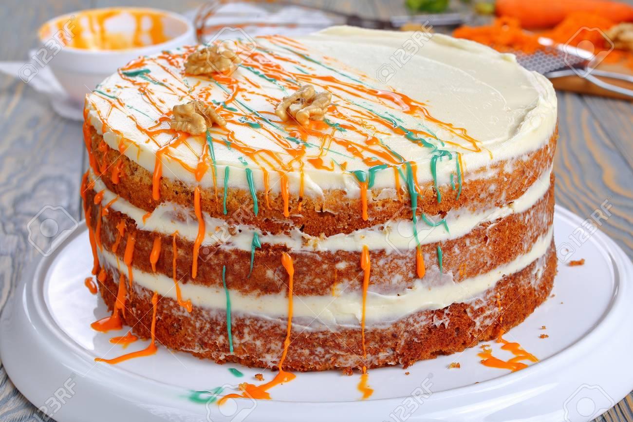 Delicioso Clásico Pastel De Zanahoria Con Glaseado De Queso Crema Decorado Con Nueces Y Rociado Con Ganache Colorido En Bandeja En La Mesa De Madera