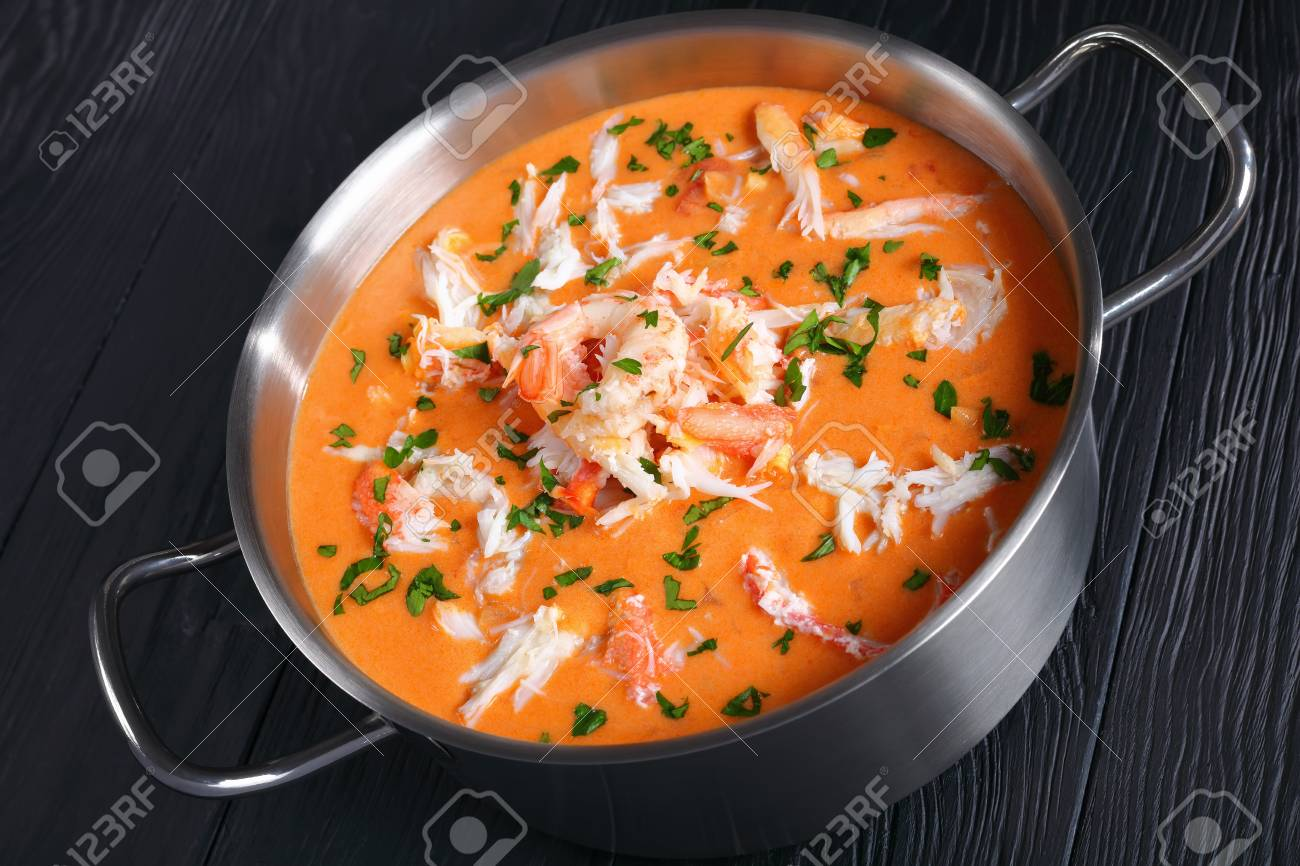 close-up of savory delicious hot bisque or thick soup of shredded snow crab meat, prawn, lobster in a stainless metal casserole on black wooden table, authentic french recipe, view from above - 95302885