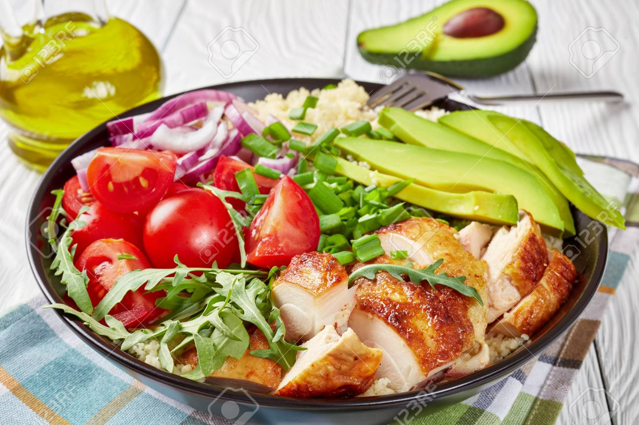 grilled chicken salad in a bowl with steamed couscous, fresh vegetables, avocado, scallion and rucola on a white wooden table with sesame oil, view from above, close-up - 120242161