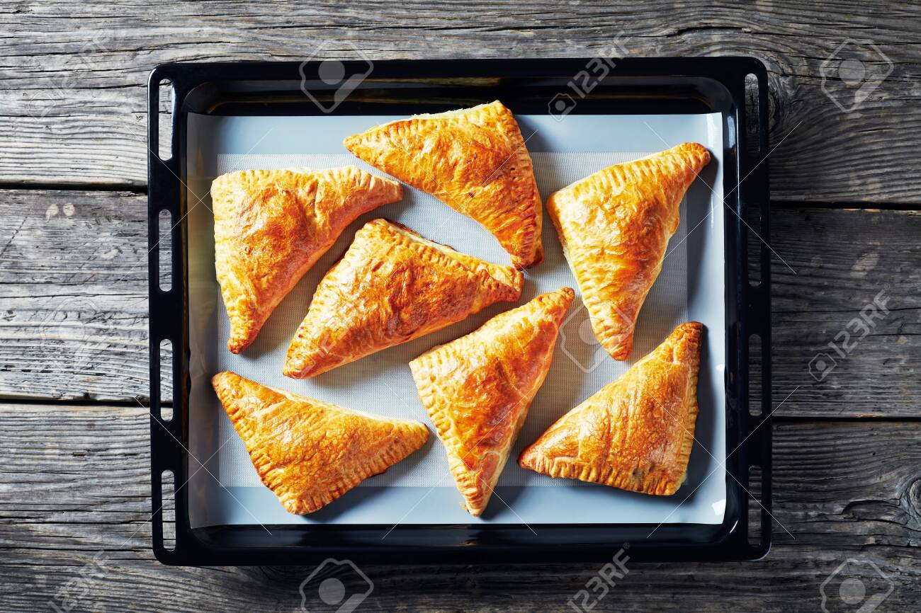 homemade freshly baked puff pastry apple turnover on a silicon mat on a baking tray, horizontal view from above, flatlay, close-up - 129700373