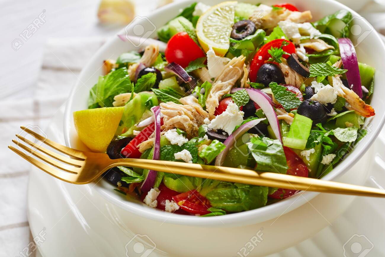 close-up of pulled chicken meat, olives, red onion, tomatoes, cucumber, mint, lettuce salad sprinkled with crumbled feta cheese in a white bowl, horizontal view from above - 150007003