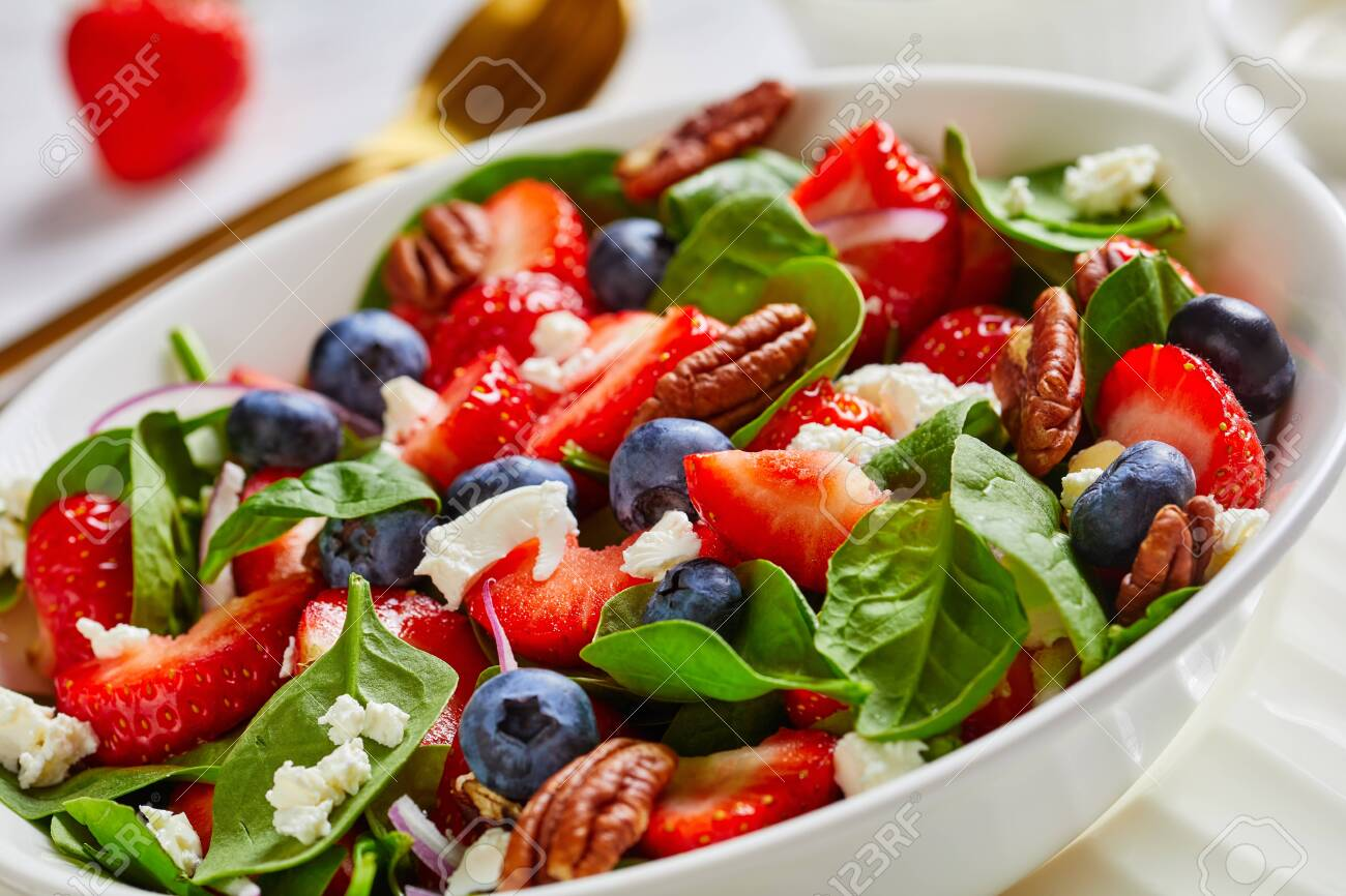 close-up of summer salad of strawberries, blueberries, spinach, pecan nuts and crumbled feta cheese in a white bowl on a wooden table, horizontal view from above, macro - 150077835