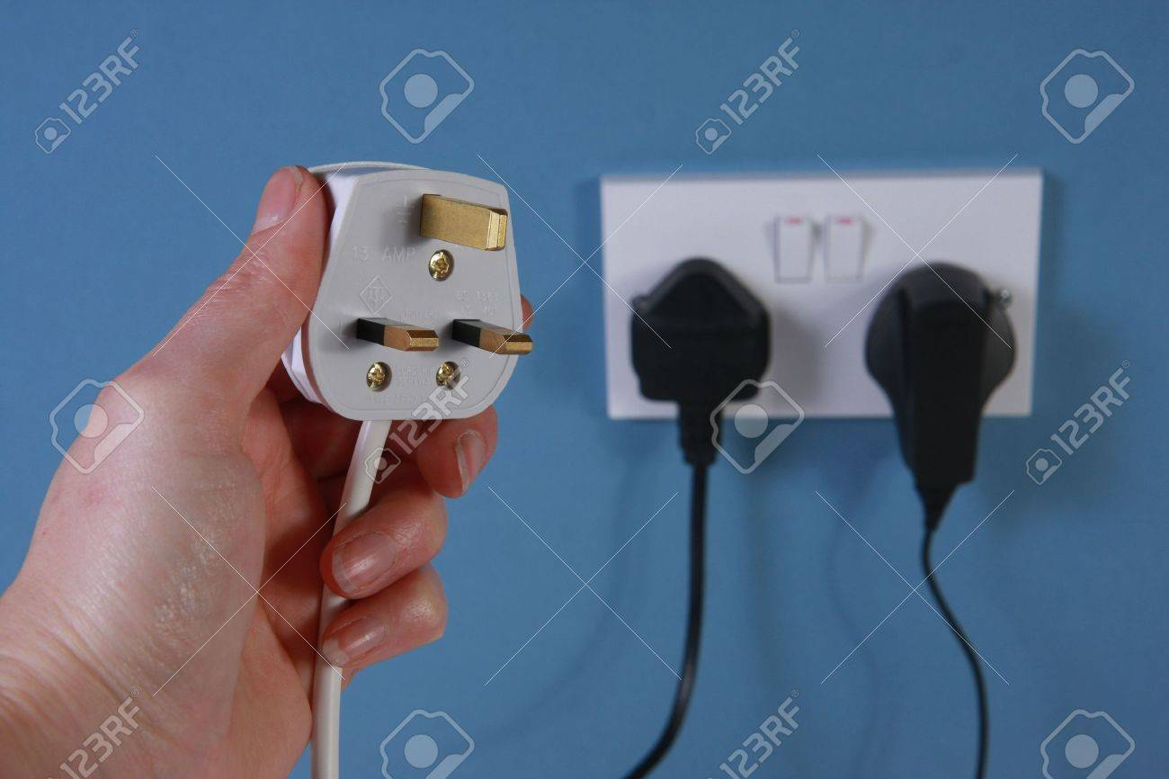 A Left Hand Holding A UK Style 3 Pin Plug With A Double Socket ...