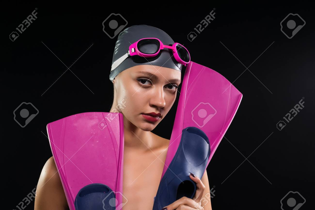 pensive girl holds flippers in hand on black background, swimming..