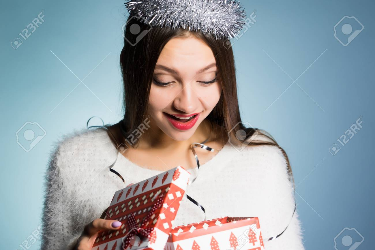 happy young girl received a gift for the new year looks in the gift