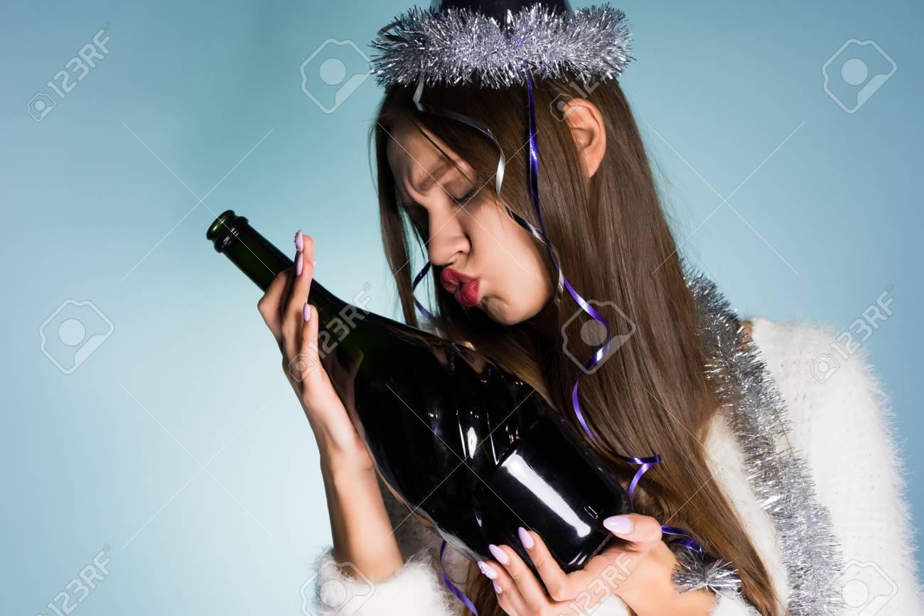 5545bd6c18 Divertida joven borracha celebra el nuevo año 2018, besa una botella de  champán Foto de