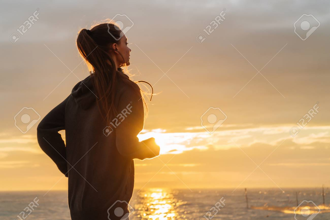 stubborn long-haired girl runs around the sea at sunset, wants to lose weight - 106644916