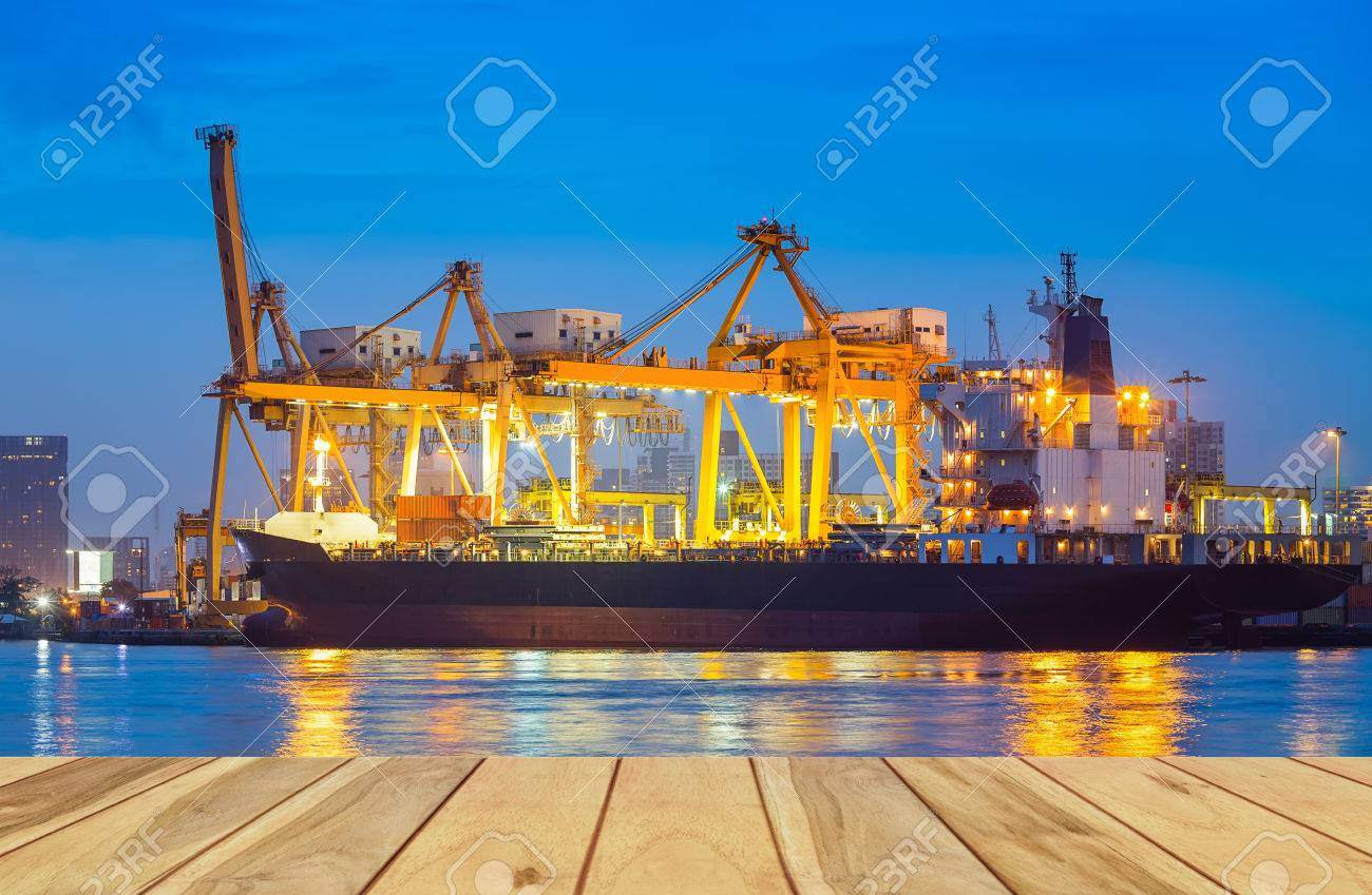 Cargo ship and crane at port reflect on river, twilight time. - 53053279