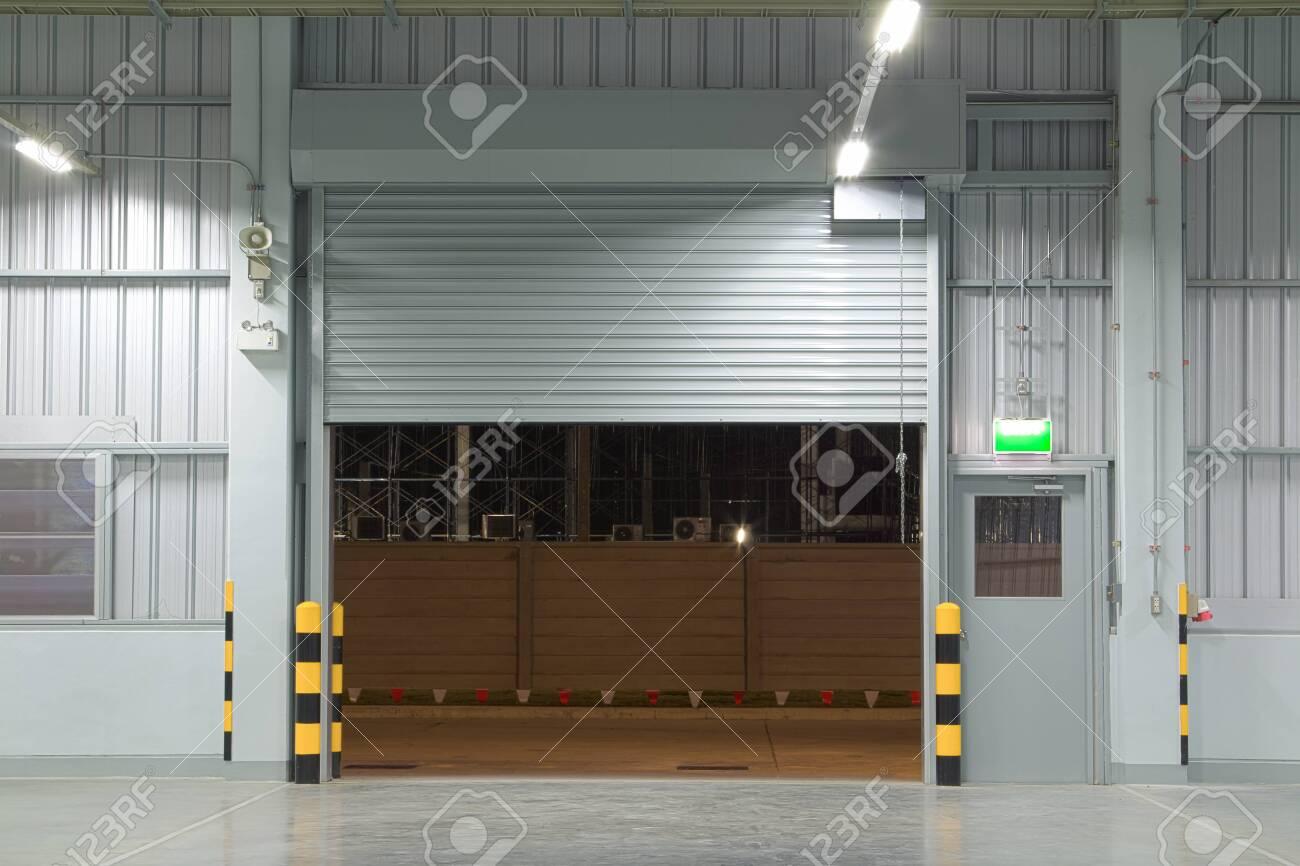 Open shutter door interior and concrete floor, night time. - 150510414