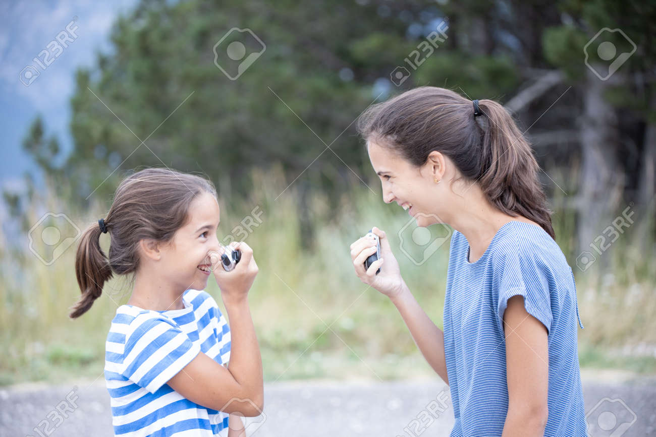 Two happy sisters very close talking and joking with a walkie-talkie - 155169194