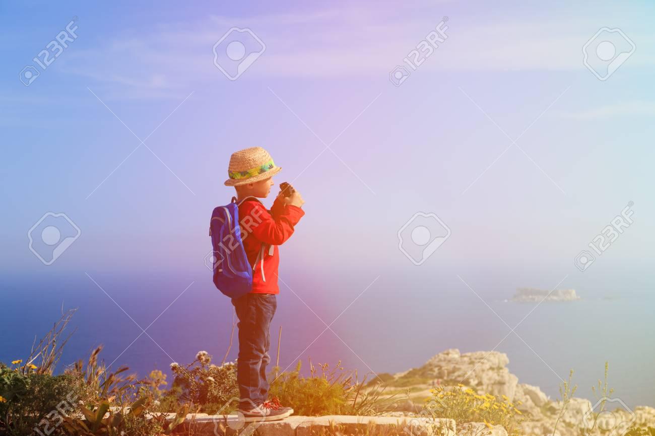 Kleiner junge mit fernglas wandern in den bergen reisen kinder